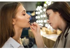 化妆师在女性身上涂口红_5863638