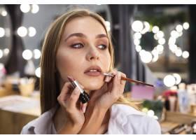 化妆师用刷子在微笑的女人嘴唇上涂口红_5863560