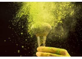 在深色背景上用化妆刷爆炸黄色粉末_4912178