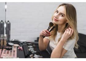 坐在工作室里拿着化妆刷的年轻女子_4298960