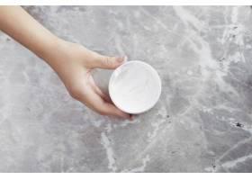 大理石背景的手持式奶油容器_5291191