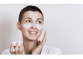 肖像年轻女子在脸上涂抹面霜_5500894