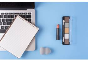 蓝色背景下的化妆品和笔记本电脑俯视图_5616960