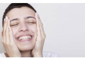微笑的女人抚摸着柔软的脸部皮肤_5500511