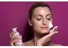 成年女性在脸上涂抹保湿霜_5445327