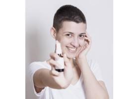 手上拿着护肤品的女人看着相机_5500518