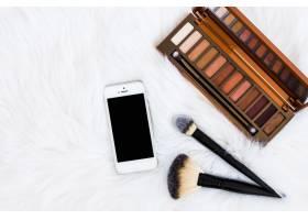 俯瞰智能手机毛皮背景上的化妆笔和眼影木_4441247