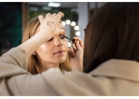 化妆师在女性身上涂睫毛膏_5863648