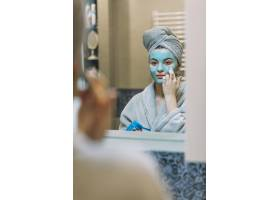 年轻女子在脸上涂抹面膜_2111005