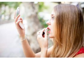 年轻漂亮的女人在户外涂胭脂_1473492