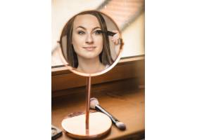 一位女士在睫毛上涂睫毛膏的倒影_2886773