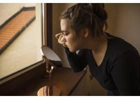 一位年轻女子在照手镜化妆时的侧视_2886943