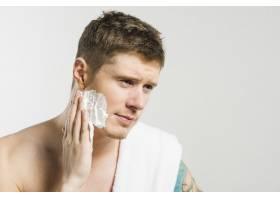 一名年轻男子在灰色背景下将剃须泡沫涂在脸_4183121