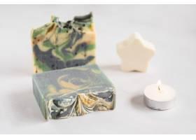 碎肥皂吧白色背景上有星星海绵和照亮的蜡_3491171