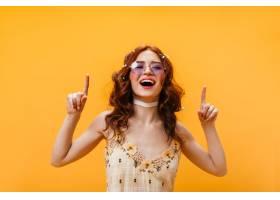 积极的女人指着上面的手指穿着黄色上衣_12677807