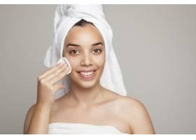 笑容可掬的女人在脸上涂棉花_1209875