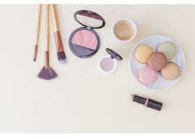 化妆刷彩色背景上有腮红口红和早餐_3029784