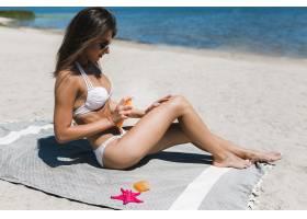 年轻女子在腿上涂防晒霜_2509449