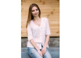 一位身穿白衬衫和牛仔裤的女子坐着_984735