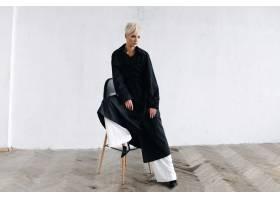 一位身穿黑色外套的模特坐在白墙前的酒吧椅_2446775