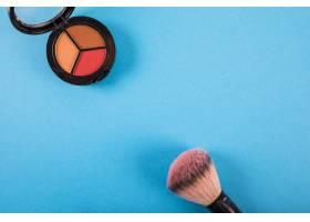 蓝色背景上刷子和腮红的高角视图_2877896