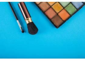 蓝色背景上的化妆调色板和画笔的提升视图_2857022