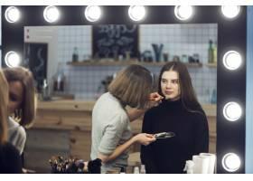 造型师在可爱的女人身上涂抹化妆品_2070568