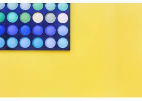 黄色背景上眼影调色板的俯视图_3019438