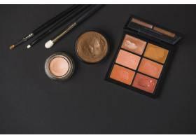 黑色背景上有画笔的彩妆产品的高角视图_3105760