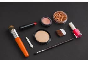 黑色背景上的化妆品和化妆刷_3100574
