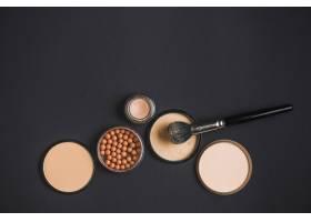 黑色背景上的化妆品和化妆刷的俯视图_3100585