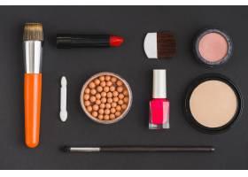 黑色背景上的各种化妆品和化妆刷_3100576