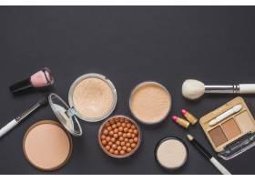 黑色表面上各种彩妆产品的俯瞰视图_3105828