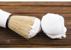 木桌上用刷子刷刮胡子泡沫的特写_4183302