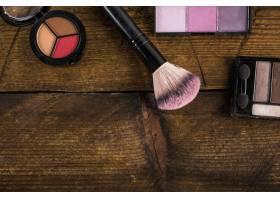 木质背景上有化妆刷的化妆品_2865978