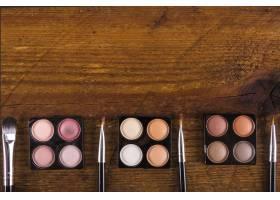 木质背景上的各式各样的化妆刷和五颜六色的_2866094