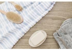 木质背景上的画笔毛巾肥皂和海绵的升高_3317968