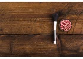木质背景上的粉球和化妆刷的高角视角_2865961