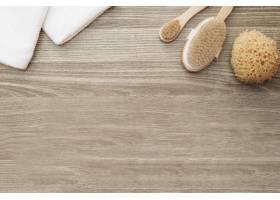毛巾的高角视角木质背景上的海绵和刷子_3317971