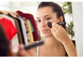 漂亮的年轻女子在家里镜子旁化妆_1624234