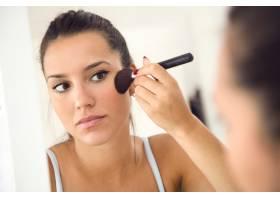 漂亮的年轻女子在家里镜子旁化妆_1624235