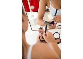 漂亮的年轻女子在家里镜子旁化妆_1624236