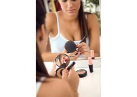 漂亮的年轻女子在家里镜子旁化妆_1624242