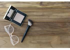 紧凑的粉末和刷子附近的眼镜_1607243