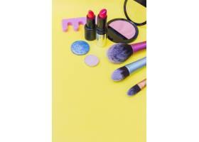 化妆刷口红和眼影黄色背景上的粉红色腮_3006353