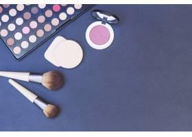 化妆刷海绵腮红蓝色背景上的眼影调色_3029862