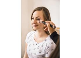 化妆师在微笑的女人脸上涂腮红的特写_2878017
