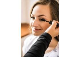 化妆师在快乐女人的脸上涂睫毛膏_2878023