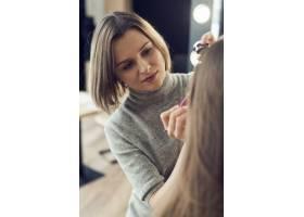 化妆师在裁剪模型上涂眼线_2092187