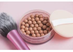 古铜色珍珠特写粉色背景上的海绵和化妆刷_3114917